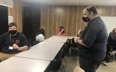 Joseph Holmberg (right) communicates with a student during an activity to practice sign language descriptors.